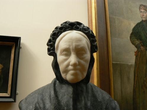 Vieille dame avec sa coiffe régionale en marbre et pierre bleue