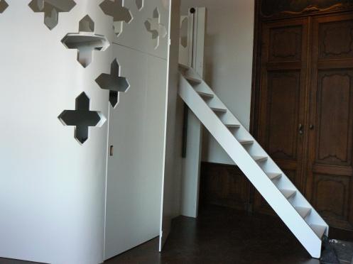 un escalier, caché derrière une porte permet l'accès à la mezzanine