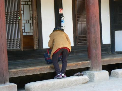 Một bà cụ đang bước lên thềm vào nhà nguyện ở đền thờ