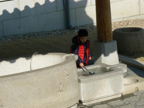 Chú bé này vọc nước chơi trong lúc bà mẹ chú cầu nguyện