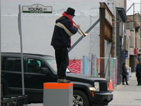 Gần quảng trường, một nghệ sĩ đường phố thổi kèn để xin tiền