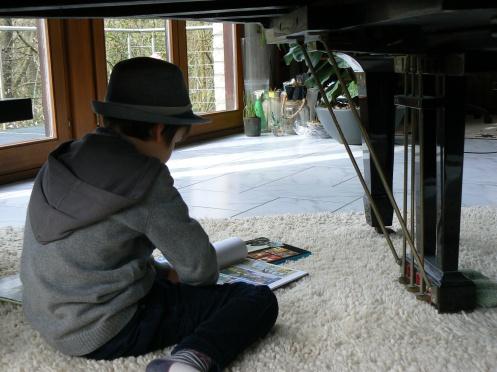 Bien protégé par son chapeau, ce garçon lit ...