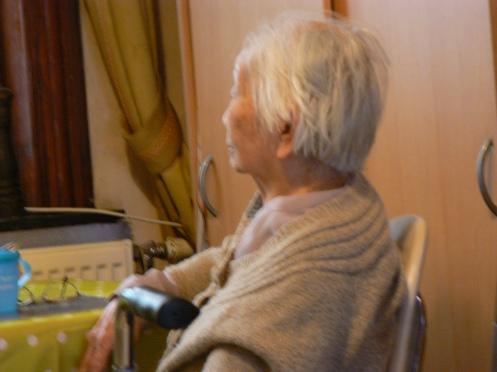 Bà cụ ngồi nhìn ra cửa sổ. Da mồi, tóc bạc ...